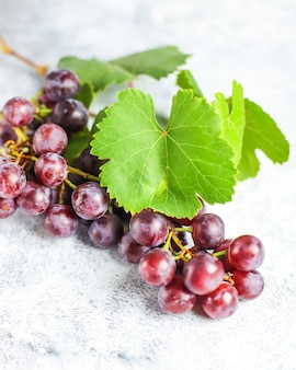 Ripe red grape with leaves on white .
