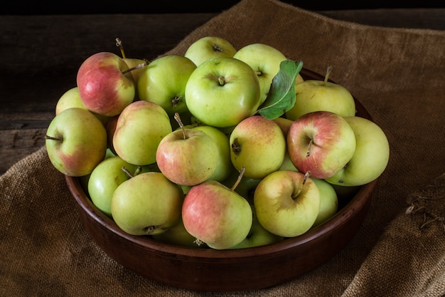 Ripe red and green apples on wooden background. apples in bowl. garden fruits autumn fruit