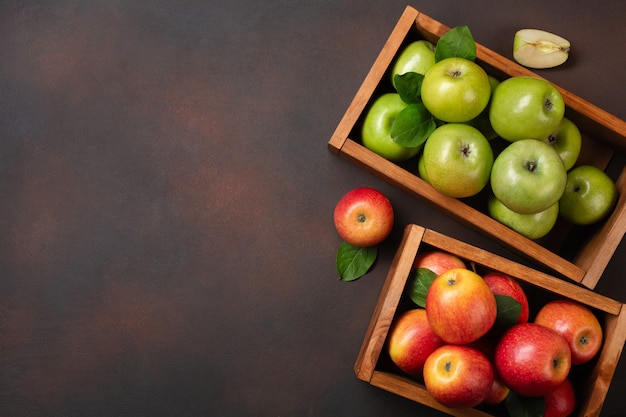 Ripe red and green apples in wooden box on a rusty background. top view with space for your text.