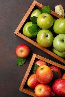 Ripe red and green apples in wooden box on a rusty background. top view.