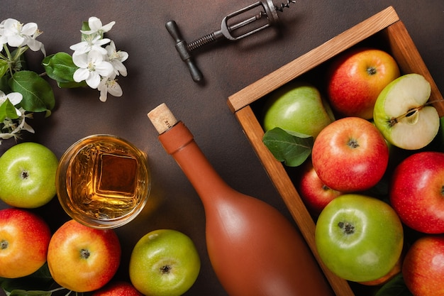 Ripe red and green apples in wooden box with branch of white flowers, glass and bottle of cider on a rusty background. top view.
