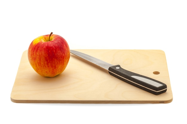 Спелое красное сочное яблоко и нож на разделочной доске из светлого дерева.