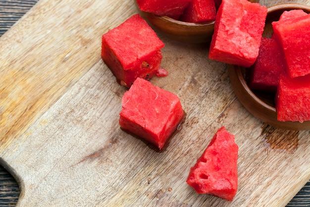 Спелый красный сочный арбуз нарезать большим количеством кусочков, красный спелый арбуз нарезать дольками.
