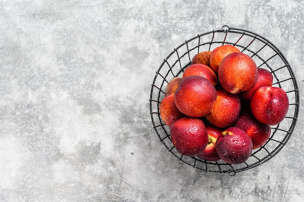 Ripe red nectarines in a basket. gray background. top view. copy space.