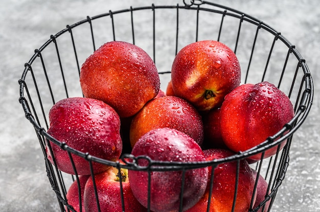 Ripe red nectarines in a basket. gray background. top view.