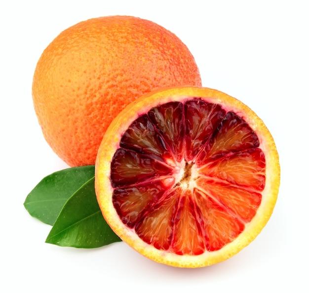 Спелый красный апельсин с листьями на белом фоне