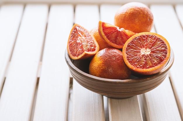 白い木製の背景に茶色のボウルに熟した赤オレンジ。スライスして熟したジューシーなシチリアブラッドオレンジ。