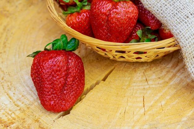 木製のテーブルに熟した赤い有機イチゴ