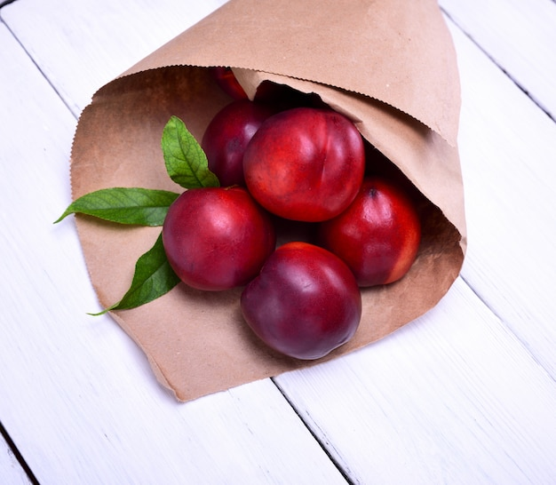 Ripe red peaches in a paper bag
