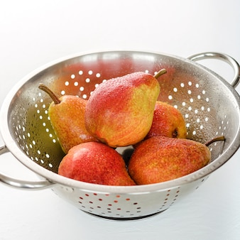 Ripe red pears on colander white background. summer fruits, harvest.