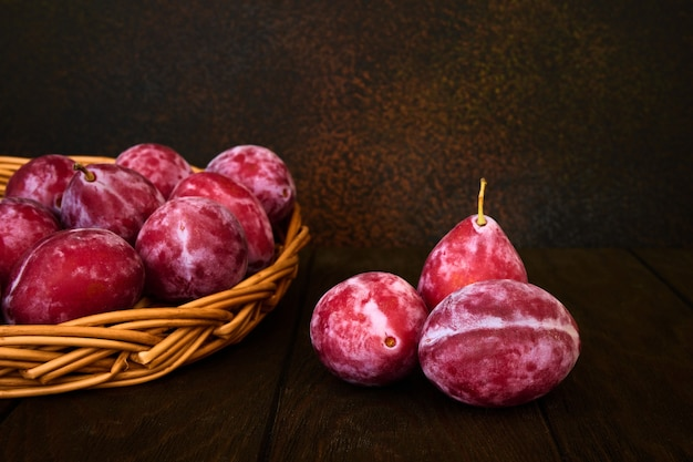 Ripe red plums on dark background with space for text