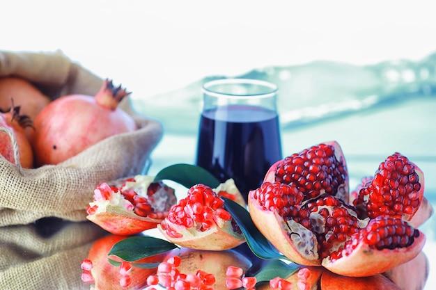 잘 익은 붉은 석류. 테이블에 잘 익은 석류 알갱이. 석류 주스.