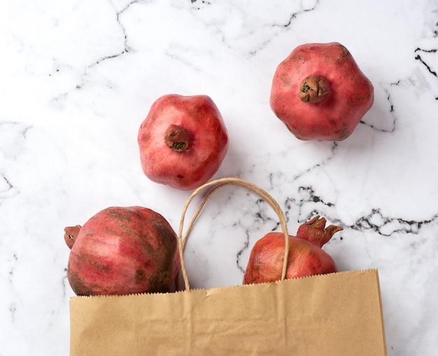 잘 익은 붉은 석류와 흰색 테이블에 손잡이가 달린 갈색 종이 봉지, 평면도