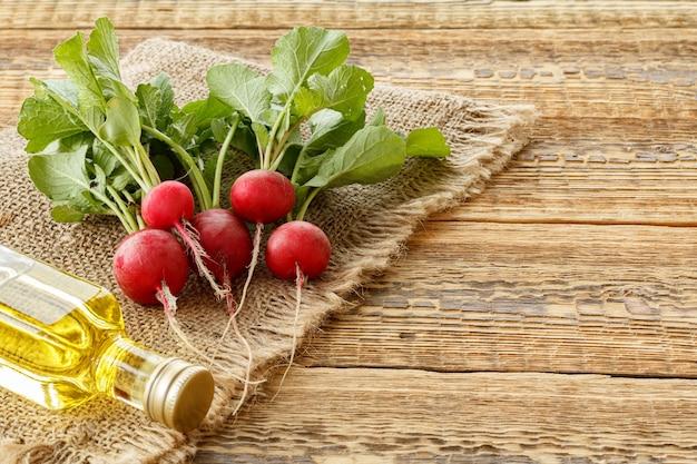 녹색 줄기가 있는 익은 붉은 무와 자루천과 오래된 나무 판자에 기름 한 병. 평면도. 정원에서 야채를 수확하는 봄.
