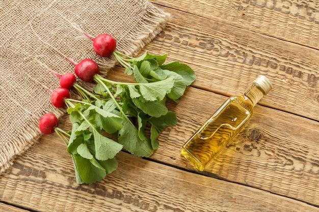 자루천에 녹색 줄기가 있고 오래된 나무 판자에 기름 한 병이 있는 익은 붉은 무. 평면도. 정원에서 야채를 수확하는 봄.