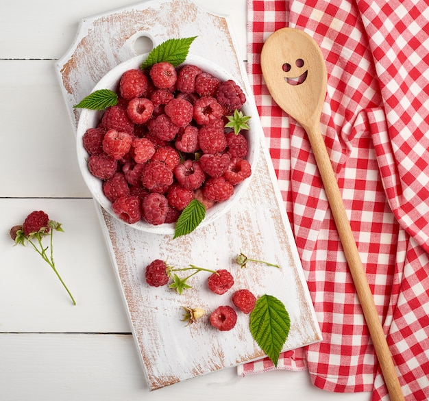 Ripe red raspberries in a white wooden plate on a table of boards
