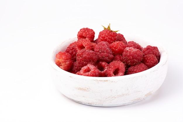 Ripe red raspberries in a wooden white plate on a white background