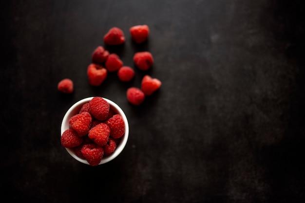 黒の背景に粘土のボウルに熟した赤いラズベリー。