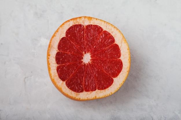 Спелый красный нарезанный грейпфрут на светлом фоне. концепция здорового питания. витамины микроэлементы. квартира лежала.