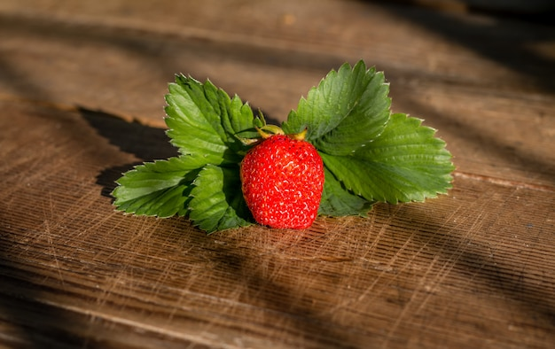 Ripe red strawberries in bowl on wooden table top view