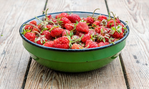Ripe red strawberries in bowl on wooden table