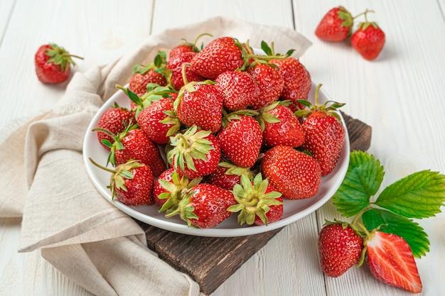 밝은 배경에 흰색 접시에 익은 빨간 딸기