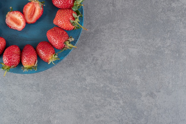 青い板に熟した赤いイチゴ。高品質の写真