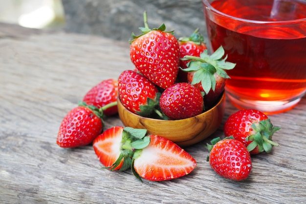 Ripe red strawberries in wooden bowls on old wood table