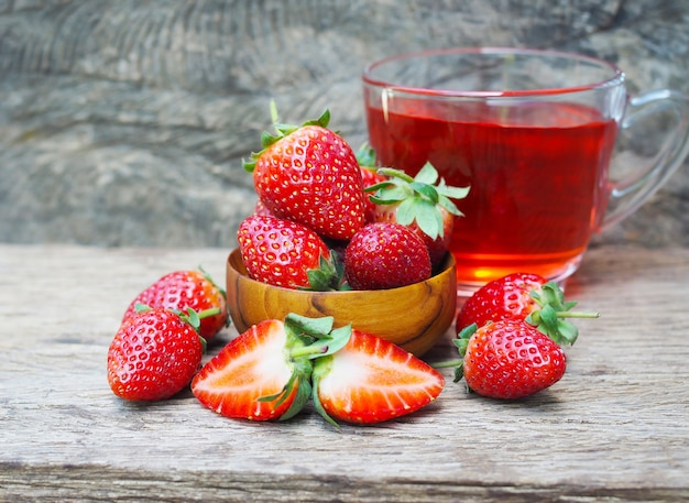 Ripe red strawberries in wooden bowls on old wooden table
