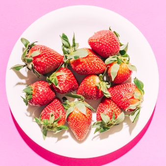 Ripe red strawberry with green stem on plate