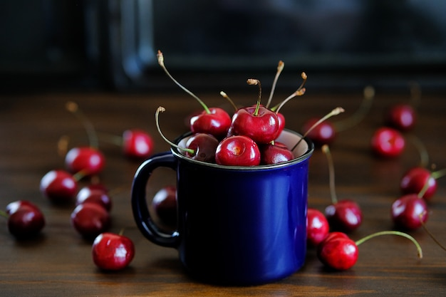 Ripe red sweet cherry in a glass on wood