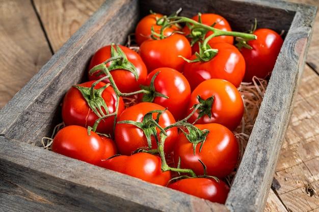 Спелые красные помидоры в деревянном ящике рынка. деревянный фон. вид сверху.