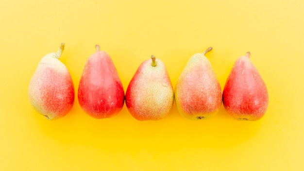 Ripe red whole pears in row
