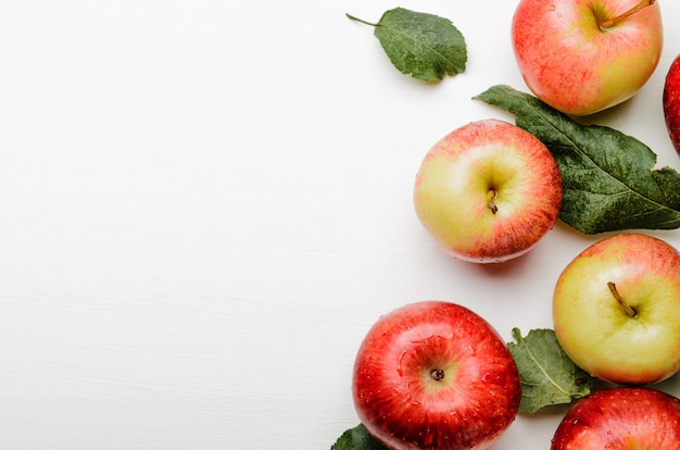 Ripe red and yellow apples with green leaves on white background.