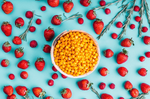 Ripe sea-buckthorn berries; strawberries and rosemary against blue background