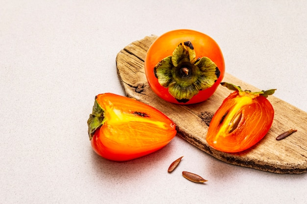 Ripe single persimmon. fresh whole fruit, half sliced, seeds. wooden cutting board,
