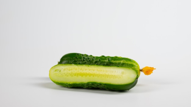 Ripe slice cucumber with flower on a white background
