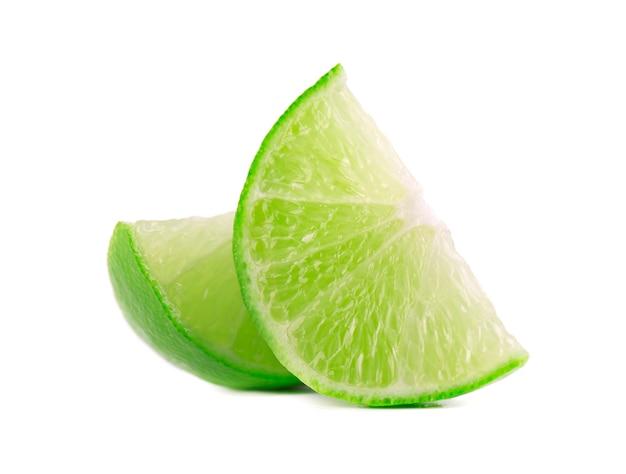 ホワイトスペースに分離された緑のライムの柑橘系の果物の熟したスライス。クリッピングパスとライムウェッジ