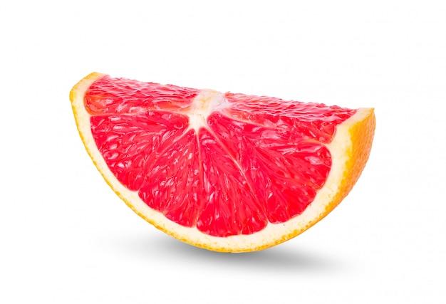 白い壁にピンクのグレープフルーツの柑橘系の果物の熟したスライス。