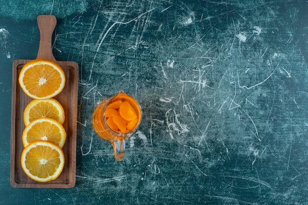 Спелый апельсин на доске, рядом с соком в графине на мраморном фоне.