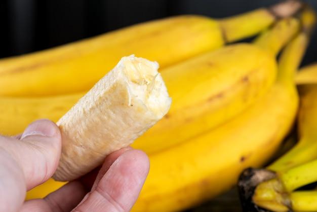 Спелый нарезанный банан в руке, ест