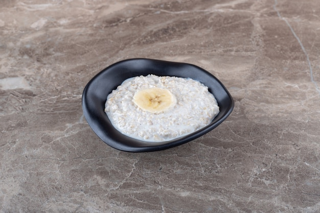 Спелый нарезанный банан на миске с кашей на мраморной поверхности
