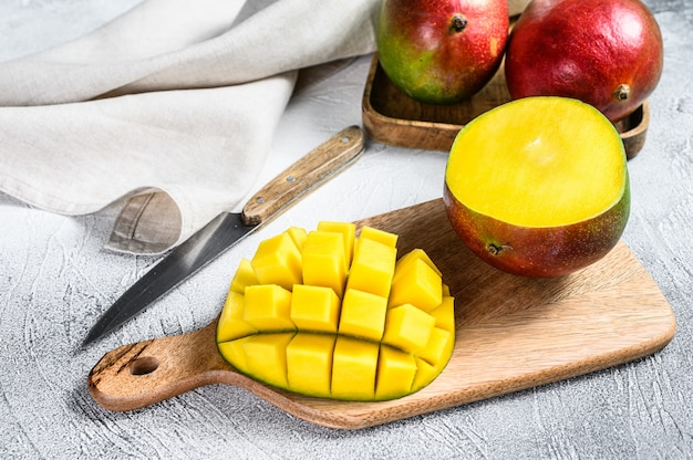 Ripe sliced mango fruit on a chopping board. gray background. top view