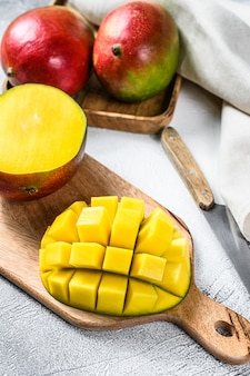 Ripe sliced mango fruit on a chopping board. gray background.