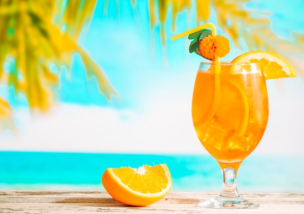 Ripe sliced orange and glass of juicy citrus drink