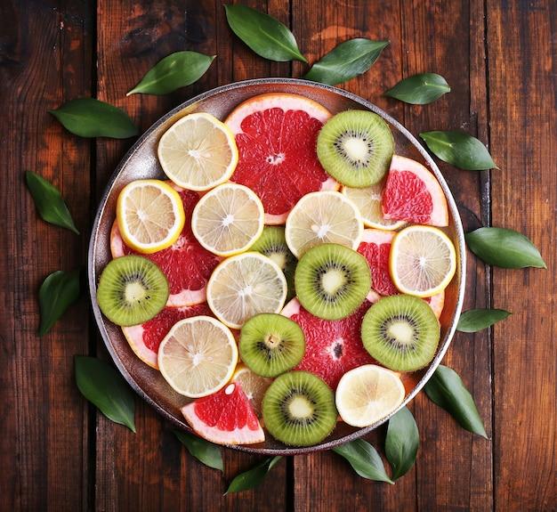 木製のトレイに熟したスライスレモン、キウイ、グレープフルーツ
