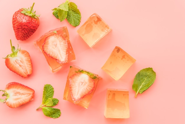 Ripe strawberries and ice pieces on background