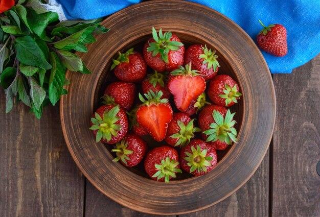 점토 그릇에 잘 익은 딸기와 민트 잎. 나무 배경. 상위 뷰