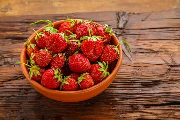 나무 테이블에 점토 접시에 익은 딸기.