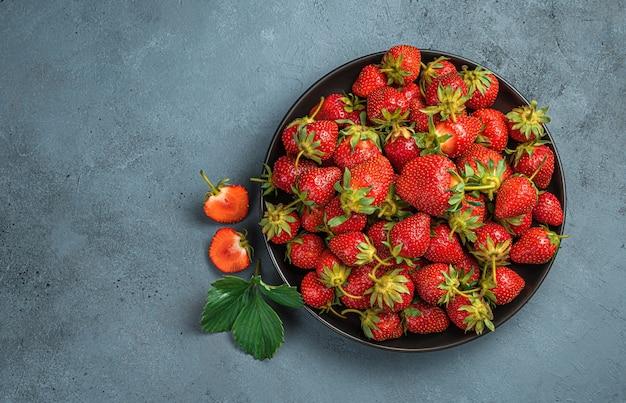 복사할 공간이 있는 회색 파란색 배경에 접시에 익은 딸기. 여름 딸기입니다.